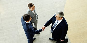 Two men shaking hands with woman looking on