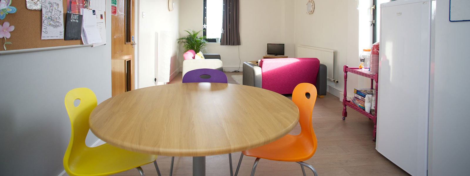 dining table with bright coloured chairs and two pink and grey couches in james young hall
