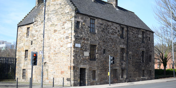an exterior shot of the oldest house in glasgow, a yellow sandstone building on cathedral street