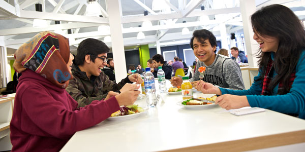 a group of students sit eating and laughing together in the Lord Todd cafe