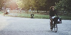 A woman rides a bike through a park