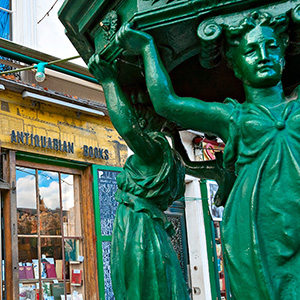 a green statue in front of a bookstore