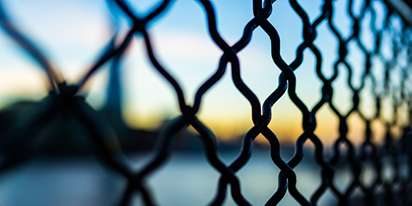 Wire fence with blurred view behind