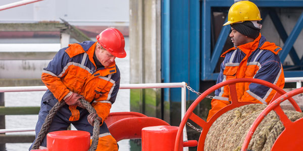 two engineers in orange high visibility pulling on ropes on a ship
