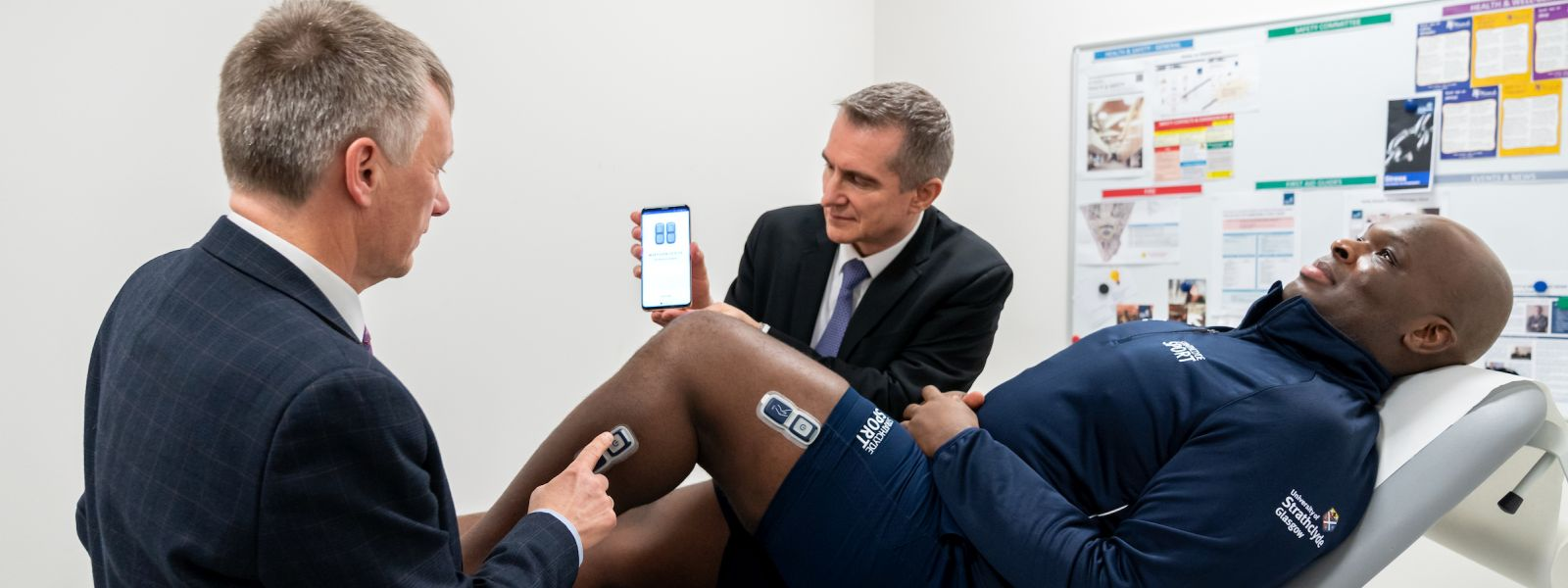 Ivan McKee, MInister for Trade, Investment and Innovation and Roman Bensen, CEO of EnMovi, demonstrate EnMovi technology on fitness instructor Jonathan Idun.
