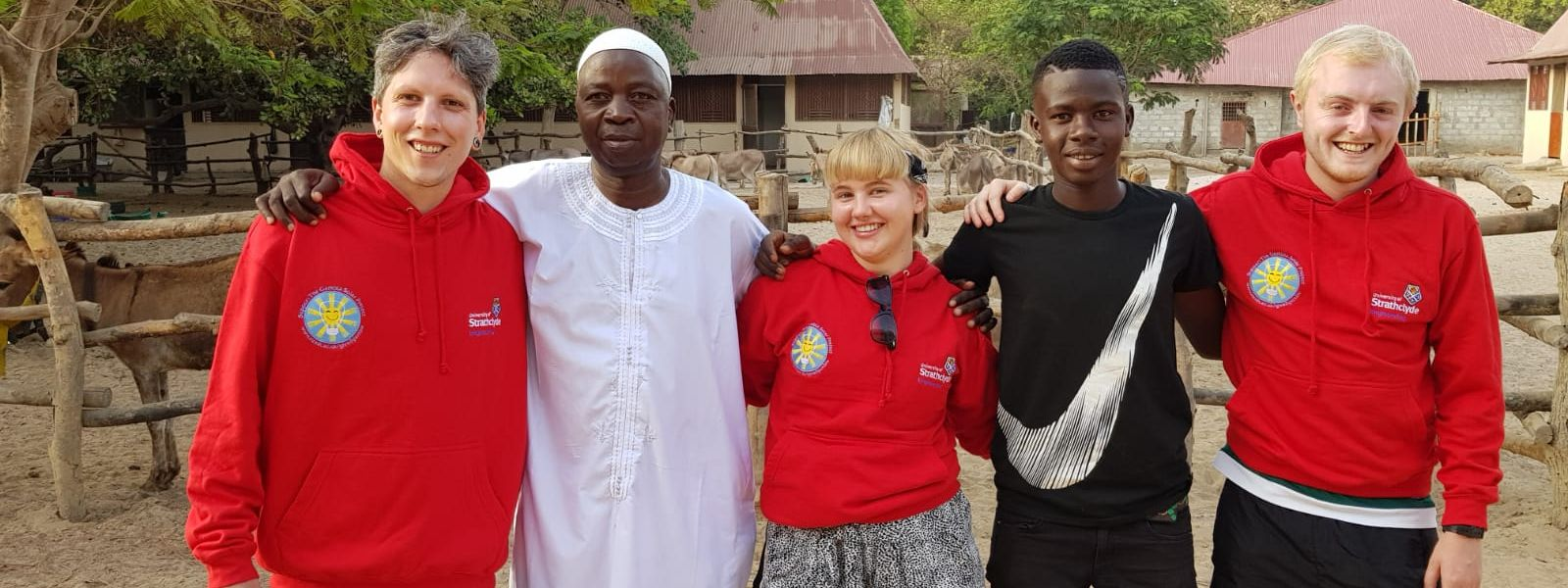 Strathclyde students Callum Taylor, Emma Tate and Steven Nolan with Kembujeh with local people in Kembujeh.
