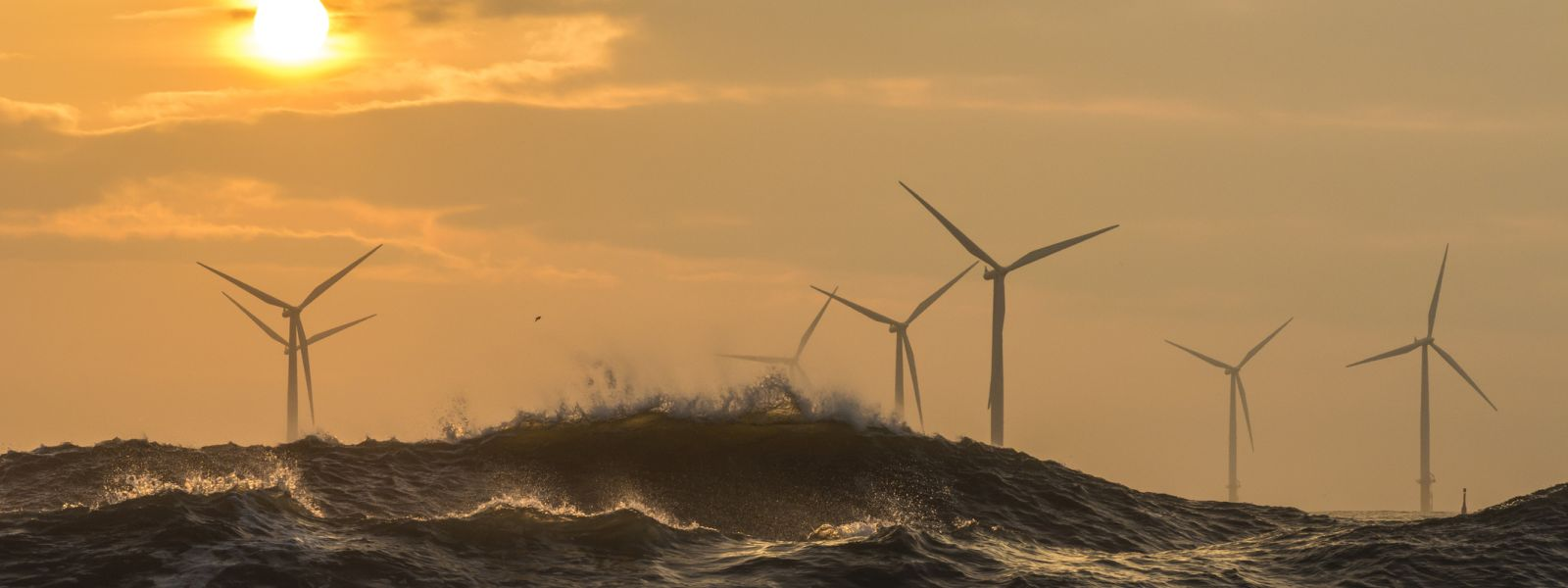 Offshore wind turbines behind large waves.