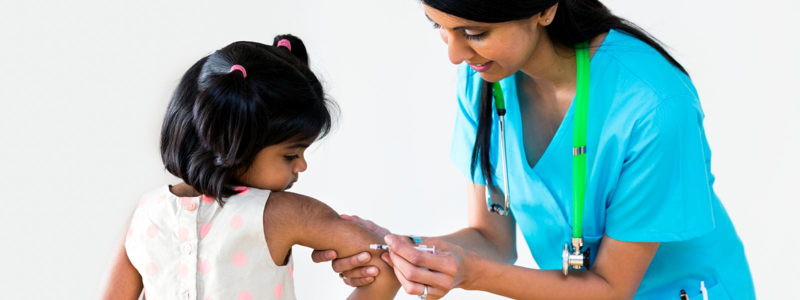 Child receiving an injection from female doctor.