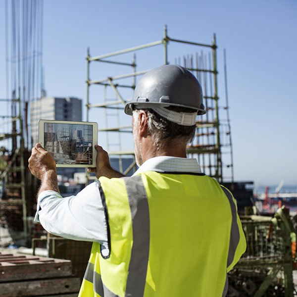 Architect photographing construction site on digital tablet