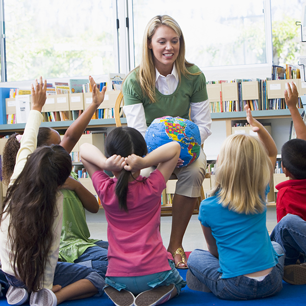 Female teacher showing world globe to young pupils