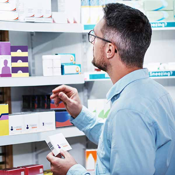 Pharmacist looking at drugs on a shelf