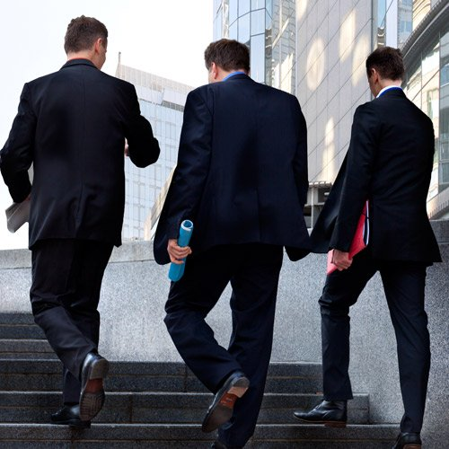 Three business men walking up stairs