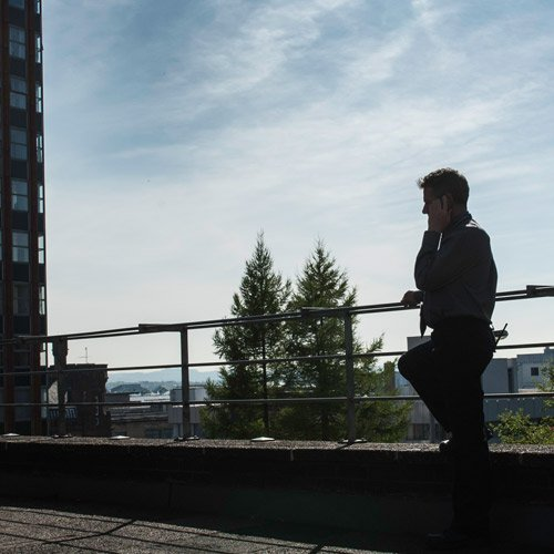 Man on phone overlooking the campus gardens
