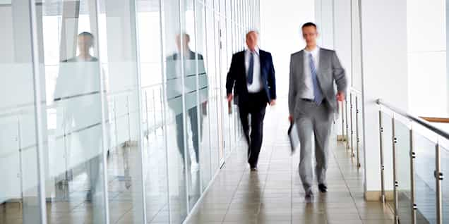 Two business men walking down a hall