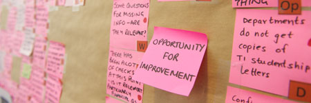 post it notes on a wall, the middle post it states opportunity for improvement