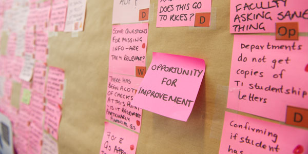 post it notes on the wall, the centre post it states 'opportunity for improvement'