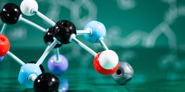 a 3D molecular structure sitting on a green surface