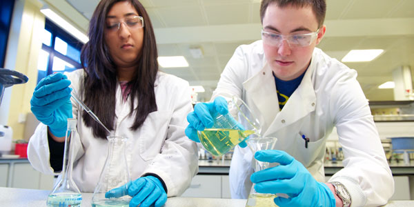 two chemistry students carrying out an experiment in a lab