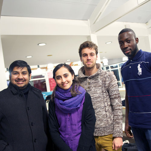 Four international students posing for a photograph at the Interfaith Dinner