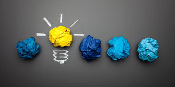 colourful balls of paper lined up with a yellow one standing out to signify a light bulb and therefore ideas