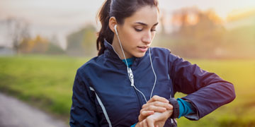 Young athlete listening to music during workout at park and adjusting smart watch. Young latin woman setting smartwatch before jogging in winter or autumn.