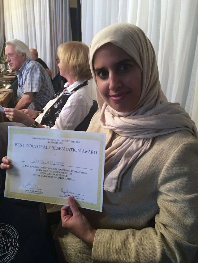Sarah Albassam, a PhD student, holds a certificate for the 'best doctoral presentation award'