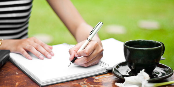 a woman sits outside writing in a journal