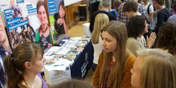 female applicant talks to a member of staff at a stand at an open day event