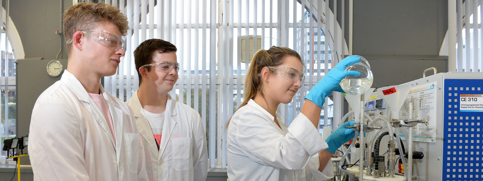 a female and two male students wearing lab coats work on an experiement