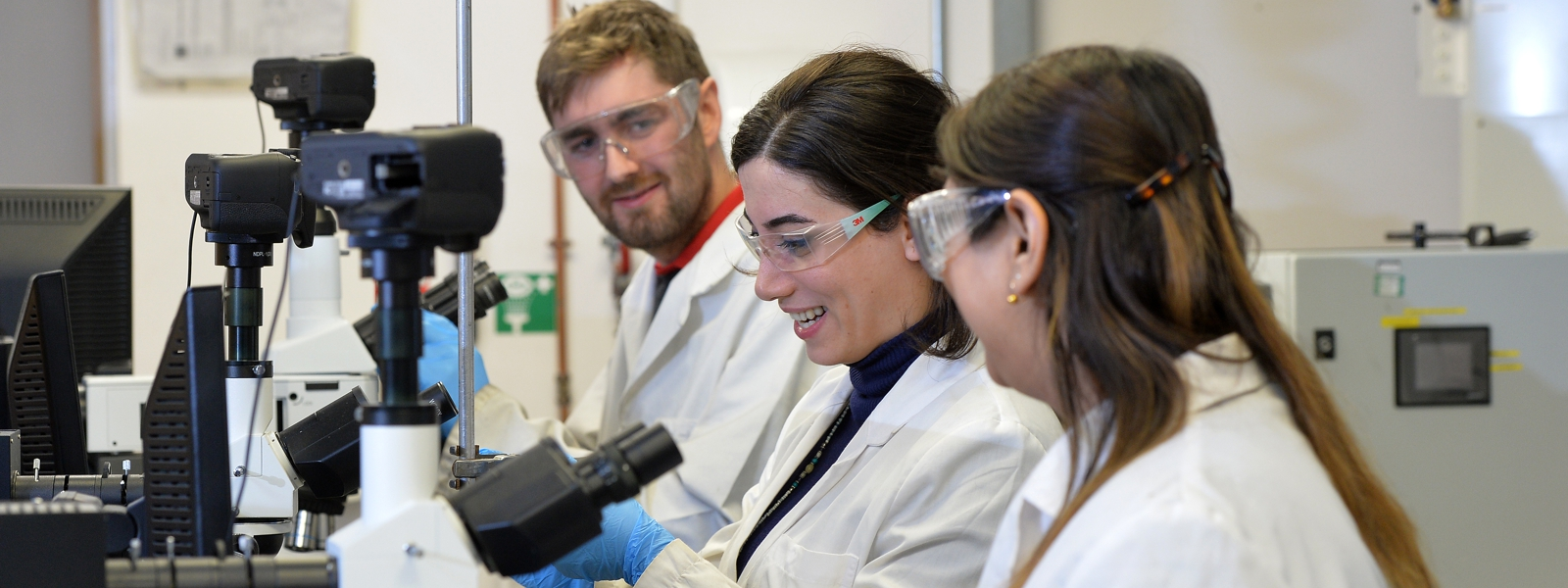 three postgraduate research students smile and work in a lab wearing lab coats