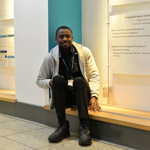 Chemical engineering PhD student Precious sitting in the James Weir corridor smiling at the camera