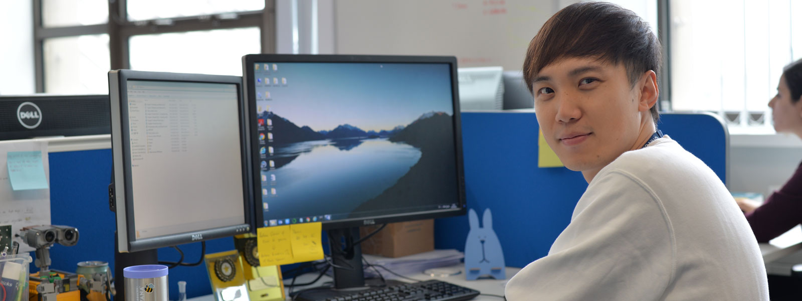 Chemical & Process Engineering PhD student Wenhan, from China, sitting at his desk, smiling at the camera
