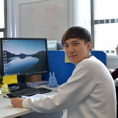 Chemical & Process Engineering student, Wenhan, from China, sitting at his desk, smiling at the camera