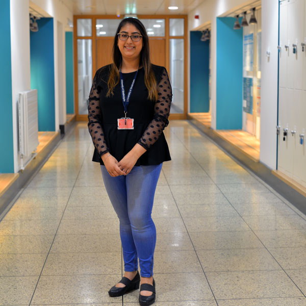 PhD student Aditi standing in the James Weir corridor smiling at the camera