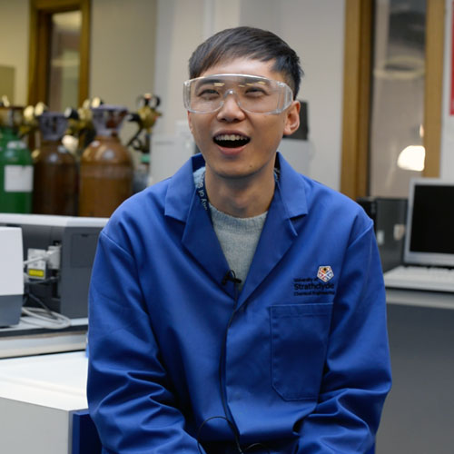 Wenhan Cao, International student from China, laughing off camera while sitting in a lab wearing a blue lab coat and lab glasses