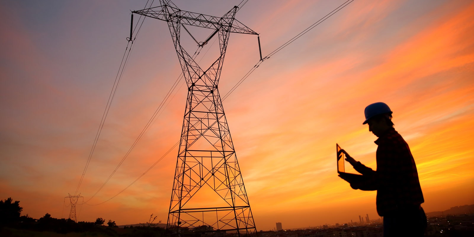 Electrical engineer stands under a pylon while working on an ipad