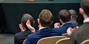 Delegates clapping at a conference