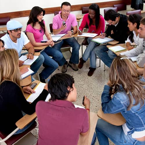 students sitting in a circle talking and taking notes