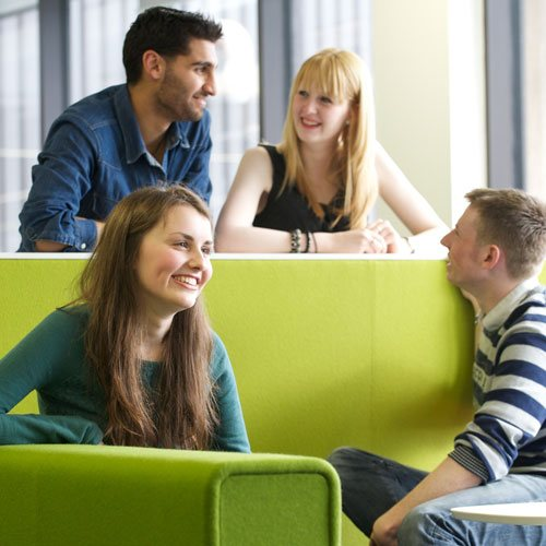 Four students sitting laughing with each other