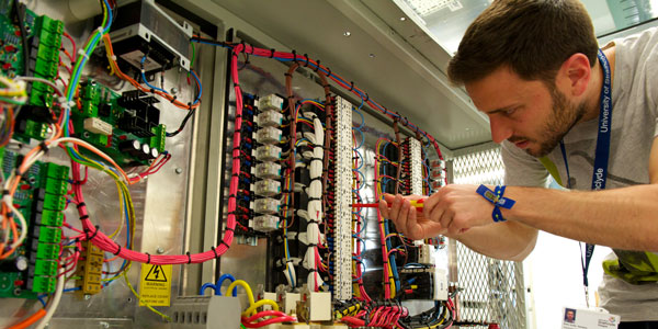 a researcher using a screwdriver on a large piece of equipment covered in colourful wires