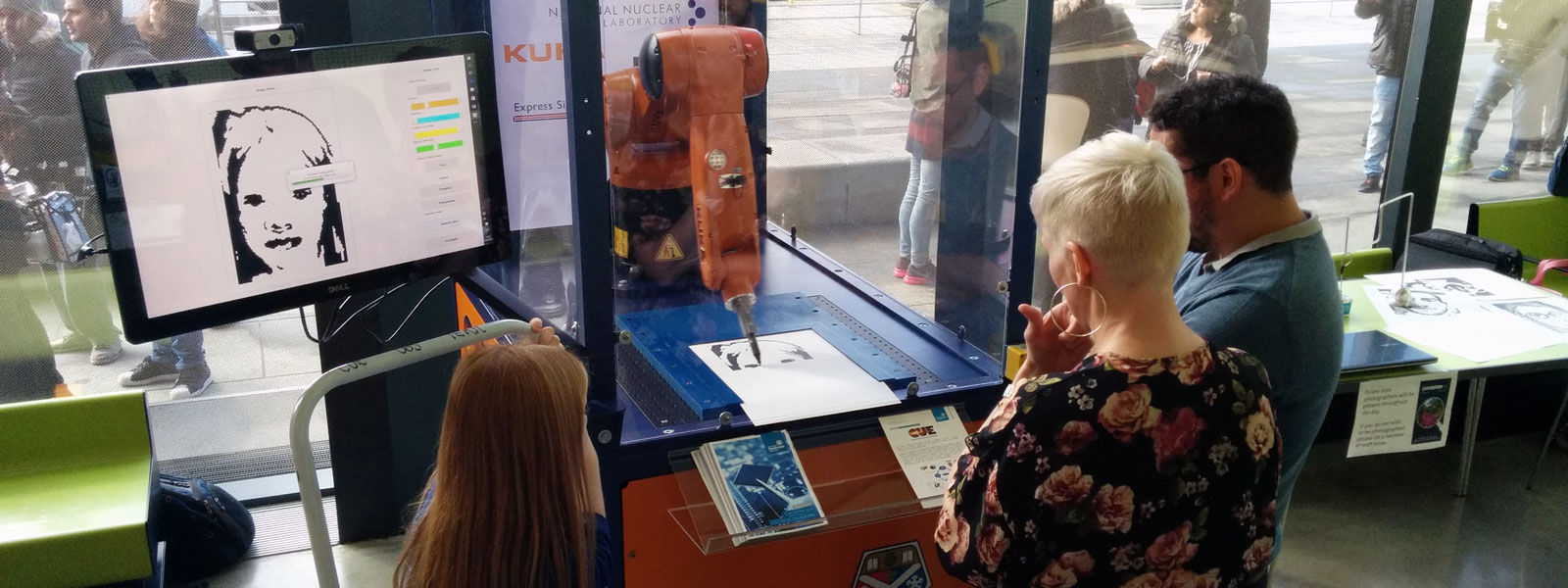people standing looking at an orange robotic arm