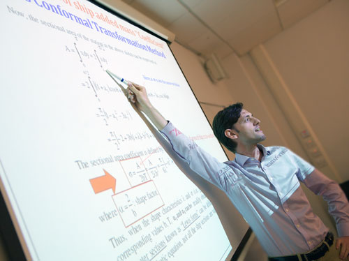 a lecturer pointing at the board