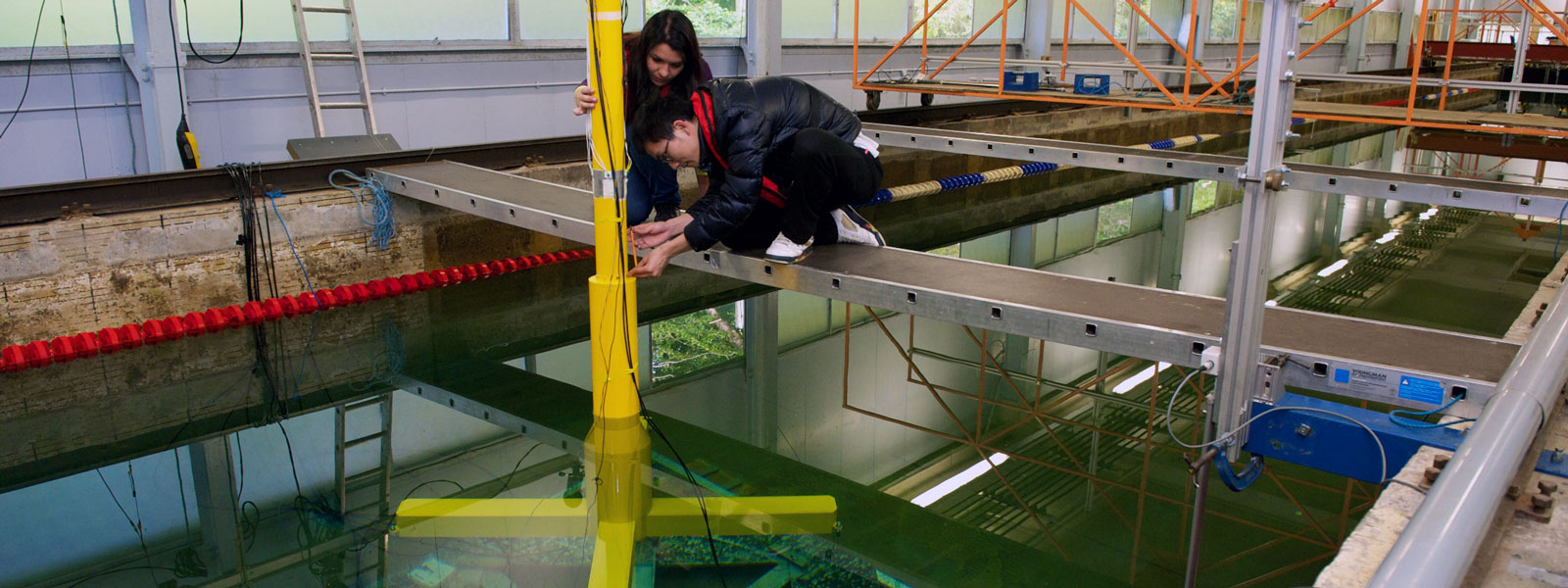 two research students fixing a yellow pole in the water