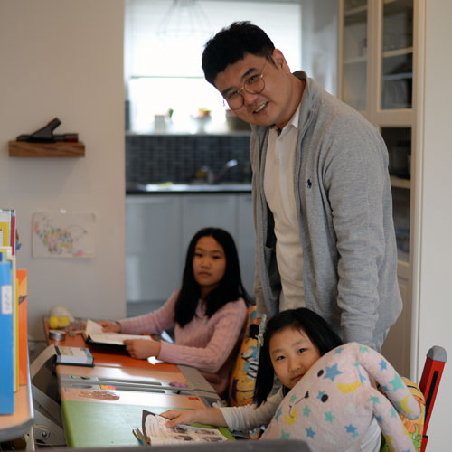 Sung il with his daughters as they sit at their desks in their living room, with Sung il standing behind them, all smiling at the camera
