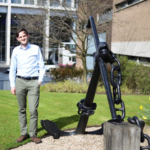 Dr Tahsin Tezdogan standing next to the anchor outside the Henry Dyer Building