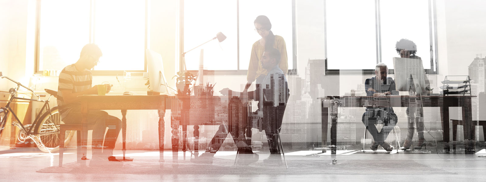 Multiple exposure shot of colleagues working in a modern office superimposed over a city background