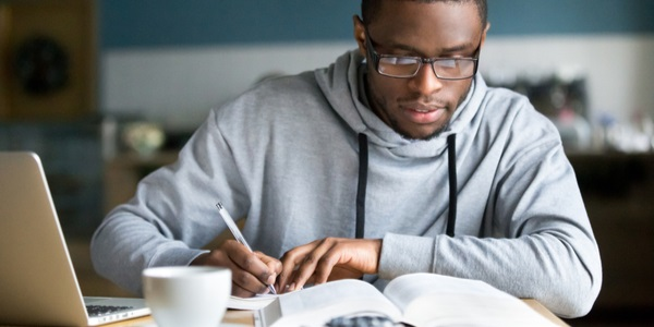 Focused millennial student in glasses making notes writing down information from book in cafe preparing for exam