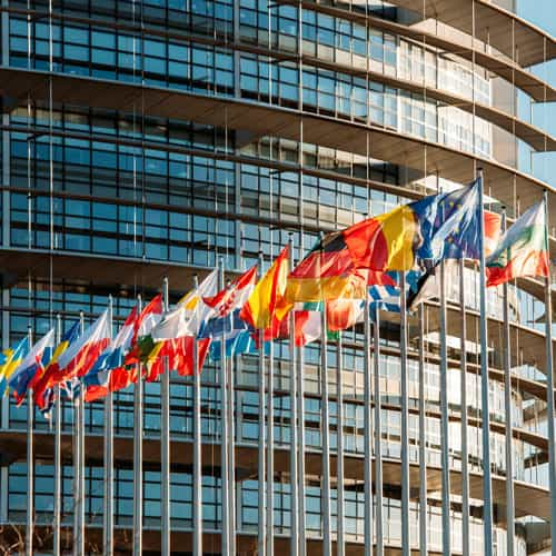 European Parliament with flags of Europe flying outside