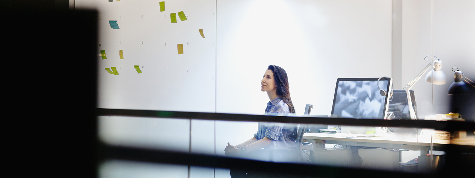 Woman looking at post-it notes on glass wall in office