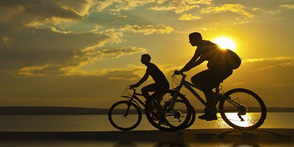 couple cycling in the sunset